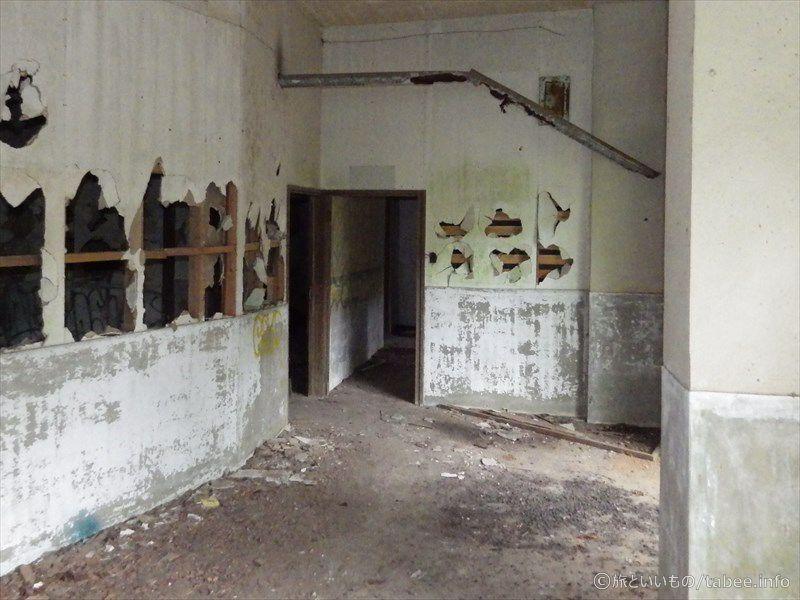 穴だらけの壁と錆びた配管